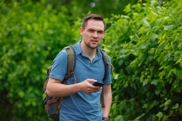 young man using mobile phone in the forest while hiking