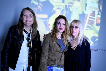 Kurt Cobain's sister Kim Cobain, his daughter Frances Bean Cobain and mother Wendy O'Connor pose for a photograph in front of a home movie of Kurt at the opening of 'Growing Up Kurt' exhibition featuring personal items of Nirvana frontman Kurt Cobain at th