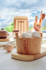 Eggs chicken, cutting boards, spoons, wooden and ceramic tableware on the table near the window for cooking baking, light background, the concept of Easter with copy space in vintage style