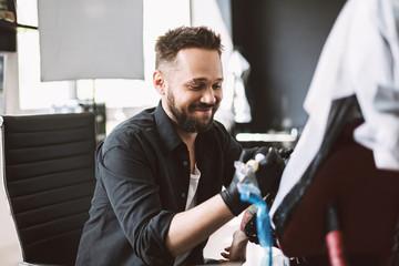 Professional tattooer happily doing tattoo on client hand using tattoo machine in modern studio