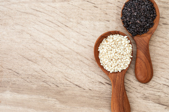 Black and white sesame seeds in a wooden spoon , top view or overhead shot