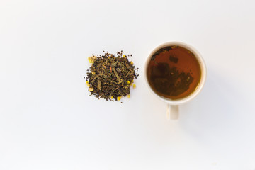 Cup of tea and dry herbal tea on a white background. Top view. Copy space
