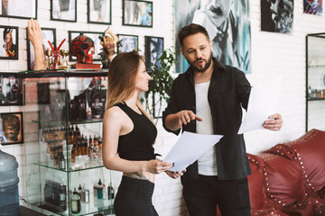 Professional tattooer and tattooed girl discussing new tattoo sketches spending time in modern studio