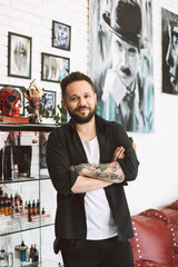 Smiling tattoo master standing with clasped hands joyfully looking in camera spending time in tattoo studio