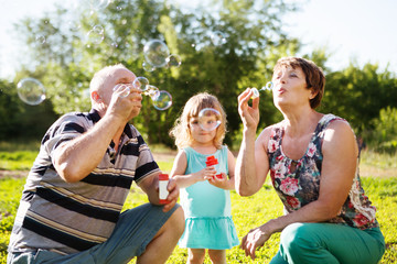 grandparents blowing soap bubbles to grandchild