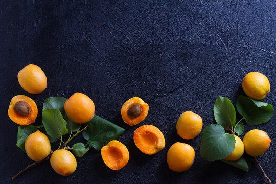 Apricots on black background, close-up. Fruit banner. Selection of healthy vegetarian food, detox or diet concept, room for text. overhead, horizontal