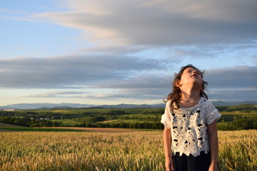 A girl looking up at the sky in a wheat field