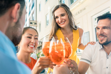 Low-angle view of a multi-ethnic group of four friends celebrating together with an orange refreshing summer drink at a trendy restaurant downtown