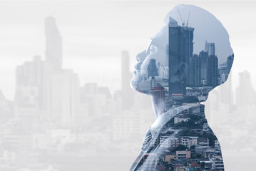 The double exposure image of the businessman thinking during sunrise overlay with cityscape image. The concept of modern life, business, city life and internet of things. Wall mural