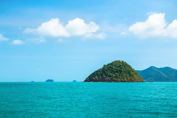Small green island of pyramid shape in the tropical sea against a blue sky with white clouds. In the background mainland.