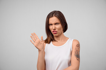 Brunette woman in casual clothes expressing disgust, unwillingness, dislike, disregard having tensive look frowning face. Cauasian woman with pleasant appearance looking indignant digusting something