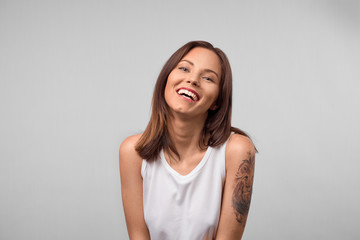 Smiling positive female with attractive look, wearing loose white T-shirt, posing against white blank wall. Happy woman with dark hair showing positive emotions after receiving pleasant compliment