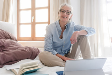 Senior woman freelancer in her study with computer sitting on the bed