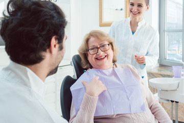 Dentist and assistant greeting senior patient in their surgery