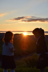 The sun setting in the mountains and two children