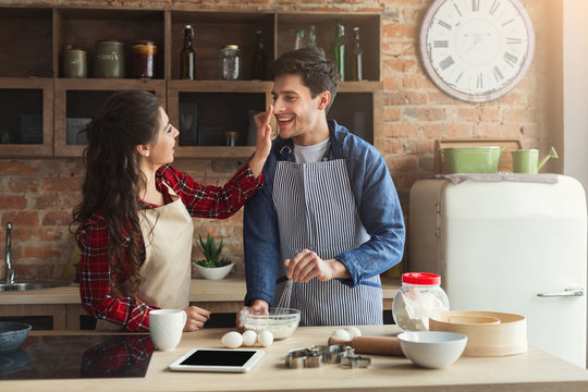 Happy young couple baking in loft kitchen