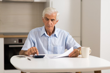 Elderly man sitting at home and calculating bills and taxes.