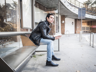 Side view of handsome stylish man in leather jacket sitting on bench on street and reading book with smile
