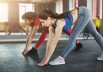 Two multiracial women exercising at fitness club