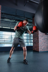 Training in gym. Dark-haired strong muscle man wearing bright red boxing gloves training in gym