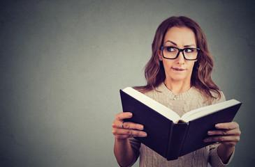 Curious nerd woman reading book