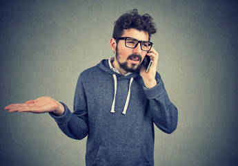 Upset young man talking on cellphone feeling annoyed and frustrated