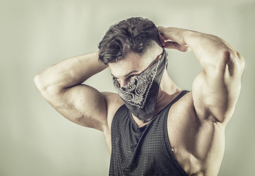Handsome muscular young man with mask over face as a robber or bandit