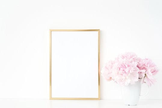 Gold portrait a4 frame mockup template with peonies in vase on white background. Empty frame mock up for presentation design, modern art.