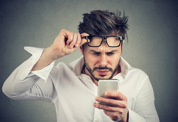 Confused man reading phone with difficulties