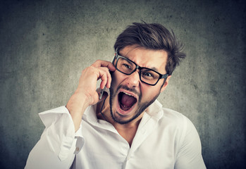 Angry man speaking on phone and yelling