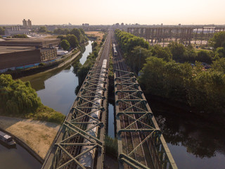 Trains crossing on a bridge above the canal river industrial landscape