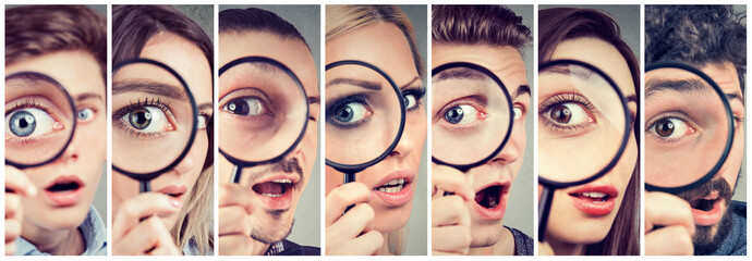 Group of curious women and men looking through a magnifying glass