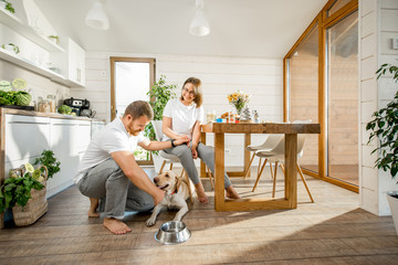 Young couple playing with dog during a breakfast in the dining room of their beautiful wooden country house Wall mural