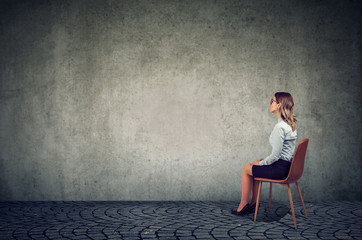 Business woman sitting on a chair in front of a wall and thinking