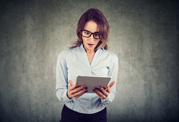 Young woman looking shocked while using tablet
