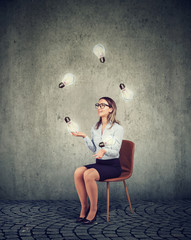 Business woman sitting on a chair playing with light bulbs