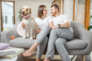 Portrait of a lovely couple sitting with their happy dog on the couch at home