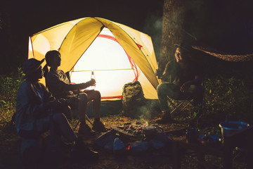 Friends are camping in the woods at night.
