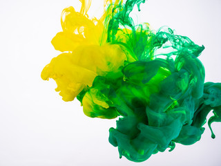 Yellow and green acrylic paint make an abstract explosion under water. Two ink colours mixing in liquid, isolated on white background. Yellow-green acrylic ink explosion under water
