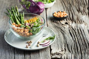 Vegetarian salad, Buddha bowl with asparagus, arugula, zucchini, kohlrabi, pistachio and chickpeas. Selective focus