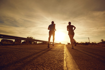 A guy and a girl jog along the road at sunset in nature. The couple is running.