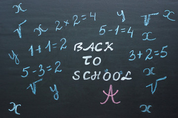 Text Back to school and mathematical examples on black chalkboar