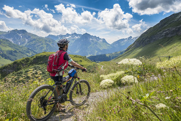 active senior woman, riding her e-mountainbike in the Arlberg area near Lech,Tirol,Austria Wall mural