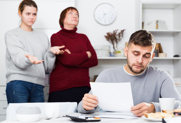 Distressed man with paperwork with irritated family behind