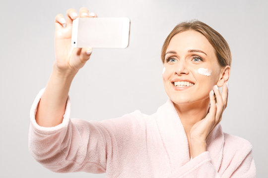 Selfie time! Portrait of young beautiful woman smiling while taking some facial cream isolated on white background with copy space.