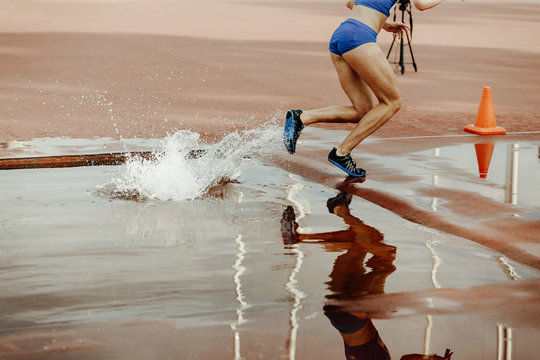 steeplechase female athlete runner overcame water jump