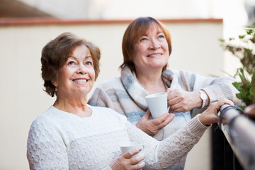 Portrait of positive cheerful female pensioners drinking tea