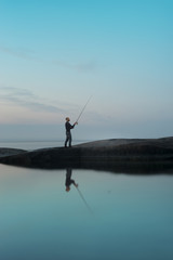 A fisherman is fishing on a stone island during the white nights