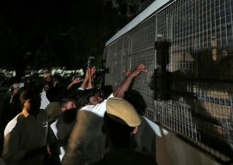 A lawyer attempts to pull the fenced window of a police vehicle carrying men (unseen) accused of raping a 12-year girl inside the high court premises in Chennai