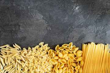 Dry pasta background. Different pasta on dark background. Flat lay. Top view.